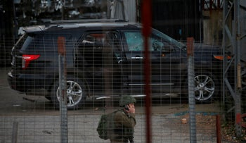 An Israeli soldier stands next to the vehicle of a 60-year-old man, after he was shot dead by soldiers in what the army said was an attempted car ramming attack near Ramallah on December 13, 2018.