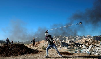 A Palestinian uses a sling to hurl stones during clashes with Israeli troops near Ramallah, December 14, 2018.