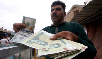 A man holds Iranian rials at a currency exchange shop in Basra, Iraq, November 3, 2018.