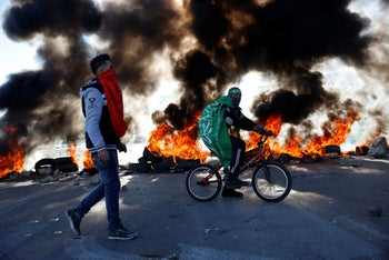 A Palestinian man wrapped in a Hamas flag rides a bike during clashes with Israeli troops at the Hawara checkpoint, south of Nablus, West Bank, December 14, 2018.