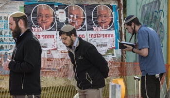 People praying near the site of the terror attack at Givat Assaf, December 13, 2018.
