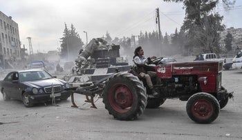File photo: A Turkish-backed Syrian fighter tows a looted vehicle with a tractor after seizing control of the Syrian city of Afrin from the Kurdish People's Protection Units (YPG), March 18, 2018.