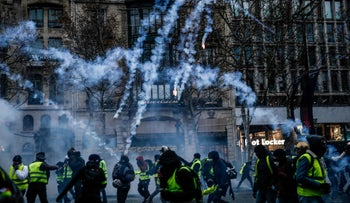 """Protesters wearing yellow vests amid smoke of tear gas during a demonstration against rising costs of living they blame on high taxes on the Champs-Elysees avenue in Paris, on December 15, 2018. - The """"Yellow Vests"""" (Gilets Jaunes) movement in France originally started as a protest about planned fuel hikes but has morphed into a mass protest against the president's policies."""