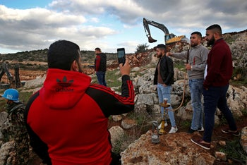 Lebanese villagers smoke a water pipe and take souvenir pictures in front of Israeli excavators, Mays al-Jabal, southern Lebanon, December 13, 2018.
