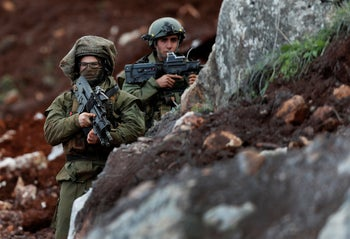 Israeli soldiers stand guard at the site of their excavation work, near the southern border village of Mays al-Jabal, Lebanon, December 13, 2018.