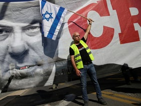 A man carrying an Israeli flag next to a banner showing Benjamin Netanyahu during a protest against the rising cost of living, Tel Aviv, December 14, 2018.