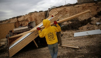 File photo: An Israeli youth builds wooden structures in the Jewish settler outpost of Amona, in the West Bank November 29, 2016.
