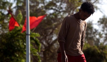 """Sudanese refugee walks past red flags fly in the city of Eilat where the municipality hung 1,500 red flags around the city as a sign of warning gainst """"the infiltration,"""" February 2011."""