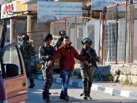 Israeli soldiers detain a Palestinian man during clashes between Palestinian demonstrators and Israeli troops in Ramallah, near the Jewish settlement of Beit El, in the occupied West Bank on December 13, 2018