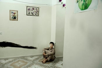 14 year-old Abdel Majeed sits on the floor at a rehabilitation center for former child soldiers in Marib, Yemen, July 25, 2018.