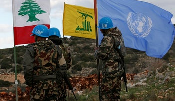 UN peacekeepers hold their flag while standing next to Hezbollah and Lebanese flags, near the border with Israel, December 13, 2018.