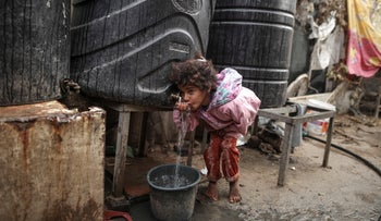 An 8-year-old Palestinian girl drinks from a water tank in eastern Gaza City, January, 2018.
