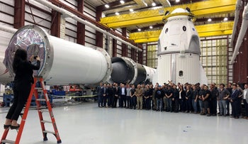SpaceX employees gather for a group photo in front of the Dragon capsule at a SpaceX hangar in Cape Canaveral, Fla., on Tuesday, December 18, 2018.