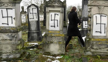 Jewish headstones tagged with swastikas at a Jewish cemetery in Herrlisheim, eastern France. December 17, 2018