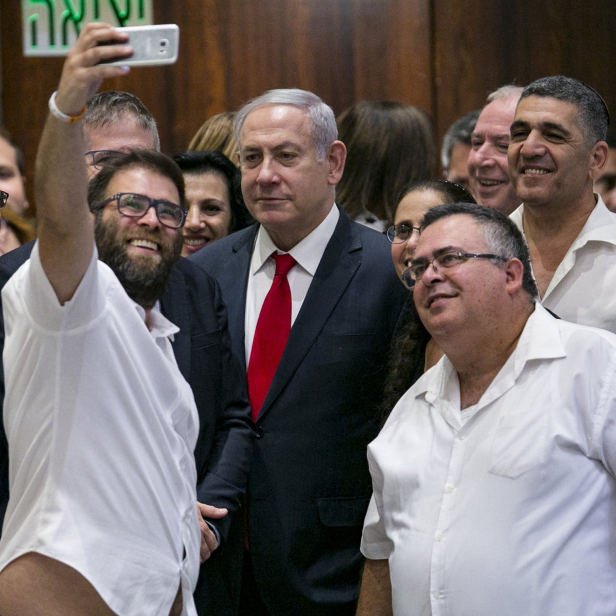 Likud MK Oren Hazan taking a selfie with Prime Minister Benjamin Netanyahu and other coalition members after a nighttime vote on the nation-state law.