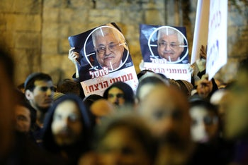 "Protesters in Jerusalem hold up posters with a picture of Palestinian President Mahmoud Abbas, calling to ""take out sponsors of terrorism,"" December 16, 2018."
