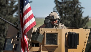 In this April 4, 2018 photo, a U.S. soldier waves as he sits on an armored vehicle, at a road leading to the tense front line with Turkish-backed fighters, in Manbij town, north Syria.