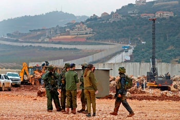 Israeli soldiers gather near excavation equipment near the northern Israeli town of Metula. Lebanese houses are seen on the hillside in the background, December 19, 2018.