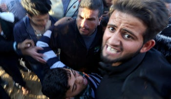 A wounded Palestinian is evacuated during a protest near the Israel-Gaza border fence, in the southern Gaza Strip December 21, 2018.