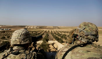 American troops look out toward the border with Turkey from a small outpost near the town of Manbij, northern Syria, on February 7, 2018.