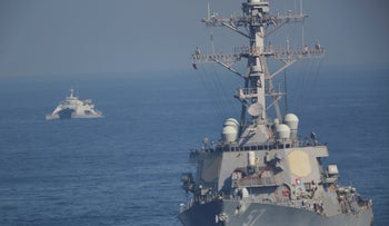 The USS Mitscher, part of a strike group led by the USS John C. Stennis aircraft carrier, sails as an Iranian Revolutionary Guard vessel shadows it on December 21, 2018.