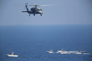 A U.S. MH-60 Seahawk helicopter flies over Iranian Revolutionary Guard patrol boats on December 21, 2018.