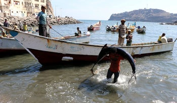 File photo: A fisherman carries a fish from a boat to a fish market in Aden, Yemen, December 13, 2018.
