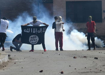 A Kashmiri man carries an Islamic State flag during clashes between protesters and Indian government forces in Srinagar, June 2018.