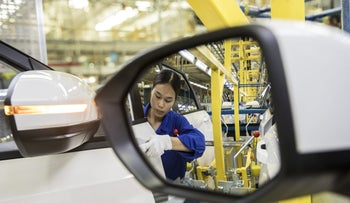 An employee inspecting a door handle is reflected in a rear mirror of a vehicle in the general assembly shop at the SAIC-GM-Wuling Automobile Co. Baojun Base plant, a joint venture between SAIC Motor Corp., General Motors Co. and Liuzhou Wuling Automobile Industry Co., in Liuzhou, Guangxi province, China, on Wednesday, May 23, 2018
