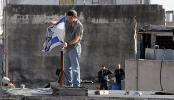 File Photo: An Israeli settler fixes an Israeli flag on the roof of a building in Hebron, January 21, 2016.