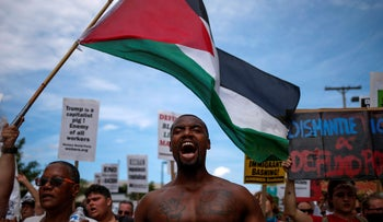 Demonstrators waving the Palestinian flag and chanting slogans during a march by various groups, including Black Lives Matter, ahead of the Republican National Convention in Cleveland, Ohio, July 17, 2016.