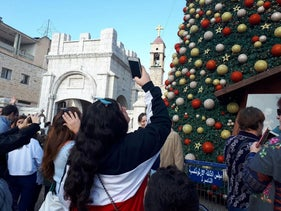 Revelers photographing the large Christmas tree situated outside the Greek Orthodox Church of the Annunciation in Nazareth, December 22, 2018.