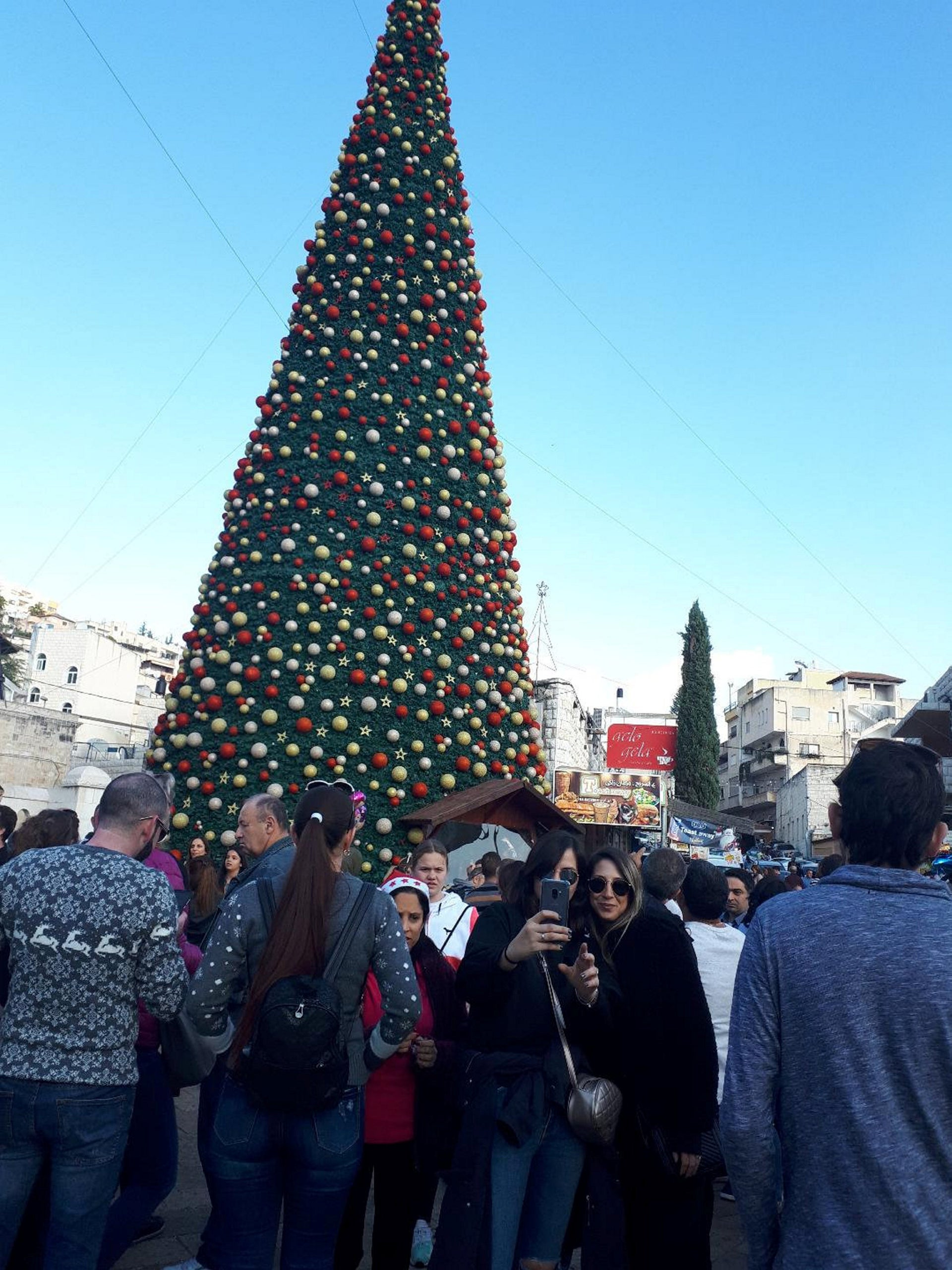 Taking a selfie in front of the large Christmas tree outside the Greek Orthodox Church of the Annunciation, Nazareth, December 22, 2018.