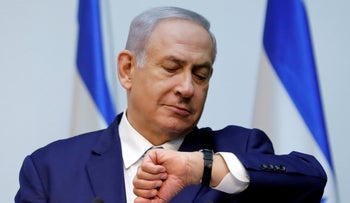 Prime Minister Benjamin Netanyahu looks at his watch before delivering a statement at the Knesset, Israel's parliament, in Jerusalem December 19, 2018.