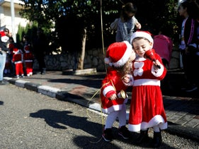 """Kids kiss each other ahead of the an annual """"Christmas Run"""" in Mi'ilya, a Christian Arab village in northern Israel December 21, 2018"""