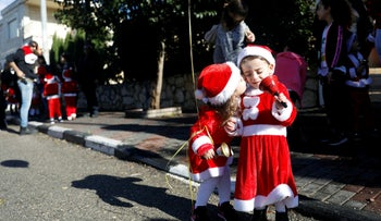 "Kids kiss each other ahead of the an annual ""Christmas Run"" in Mi'ilya, a Christian Arab village in northern Israel December 21, 2018"