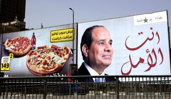 Election billboard for Egyptian President Abdel-Fattah al-Sissi hangs next to an advertisement for pizza, Cairo, March 19, 2018.