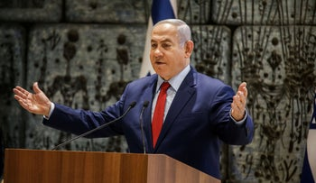 Netanyahu, wearing a blue suit, light blue shirt and red tie