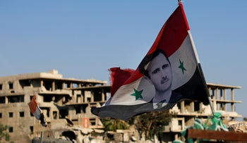 A Syrian national flag with a picture of Syrian President Bashar Assad flies at an army check point in the town of Douma, July 2018.