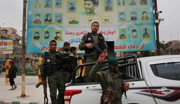 File Photo: Members of the Kurdish internal security forces stand on their vehicle in front of a giant poster showing portraits of fighters killed fighting against the Islamic State group, in Manbij, north Syria, March 28, 2018.