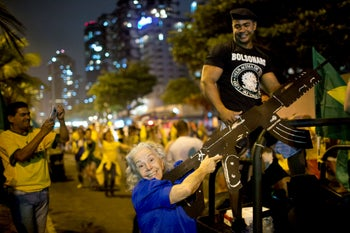A supporter of presidential candidate Jair Bolsonaro poses for a photo with a mock rifle as she celebrates the election runoff results in Rio de Janeiro, Brazil. Oct. 28, 2018