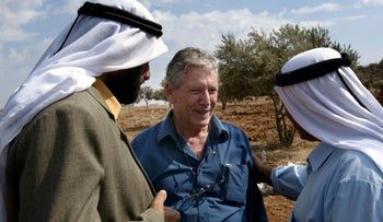 Amos Oz talks with Palestinian men after picking olives in the West Bank village of Aqraba, south of Nablus. October 30, 2002