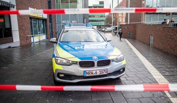 A picture taken on January 1, 2019 in Bottrop shows a police car in a cordoned off area at the site where a man injured four people after driving into a group celebrating the new year, in what police described as an anti-migrant attack.