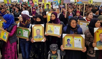 Kurdish protesters holding portraits of loved ones who died fighting ISIS, during a protest outside a U.S.-led coalition base, in Jalabiya village, southeast of Kobani, Syria. Dec. 20, 2018