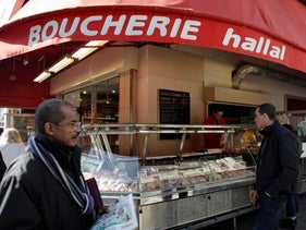 A man walking past a butcher shop in Paris which advertises that it sells Halal meat.