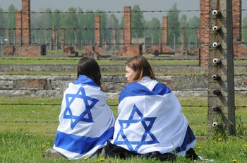 File photo: Two girls draped in Israeli flags sit in front of a barbed wire fence in the former German Nazi death camp Auschwitz-Birkenau in , Poland, May 5, 2016.