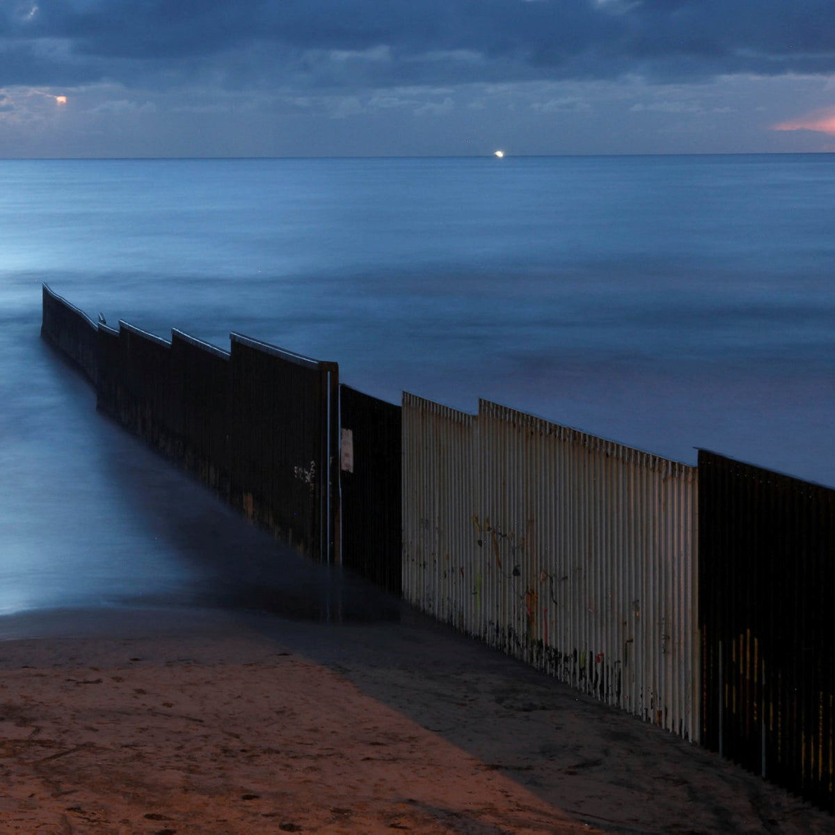 In this Feb. 28, 2018 photo, the sun sets over the U.S.-Mexico border wall that runs into the Pacific Ocean in Tijuana, Mexico. Mexico's government has refused to pay for a new U.S. border wall, a campaign promise by President Donald Trump.