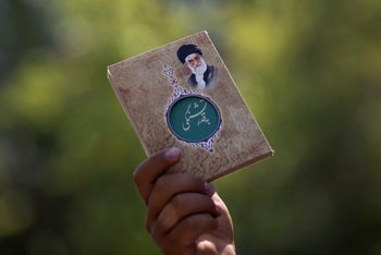 A man holds up a book of quotes from Ayatollah Ali Khamenei, Iran's supreme leader, outside Friday prayers at the University of Tehran in Tehran, Iran. Aug. 21, 2015
