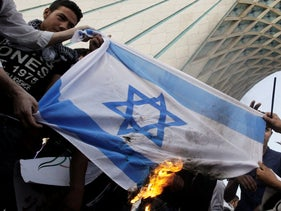 Iranian men burn an Israeli flag, in a pro-Palestinian demonstration, under the Azadi (Freedom) tower, in Tehran, Iran. May, 15, 2012