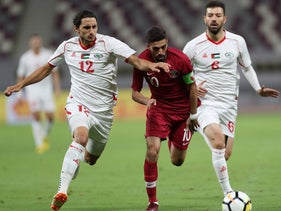 Qatar's forward and captain Hasan al-Haydos (C) vies for the ball against Palestine's Shadi Shaban (R) and Mahmoud Eid (L) during a friendly football match between Qatar and Palestine national team in Doha, September 11, 2018.
